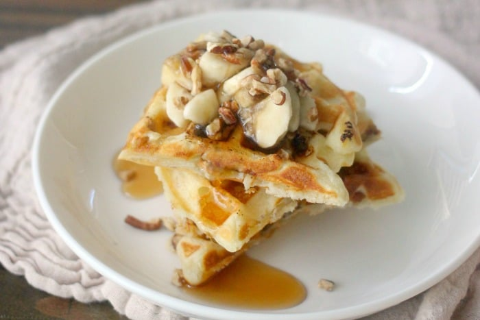 Waffles topped with banana, pecans and syrup