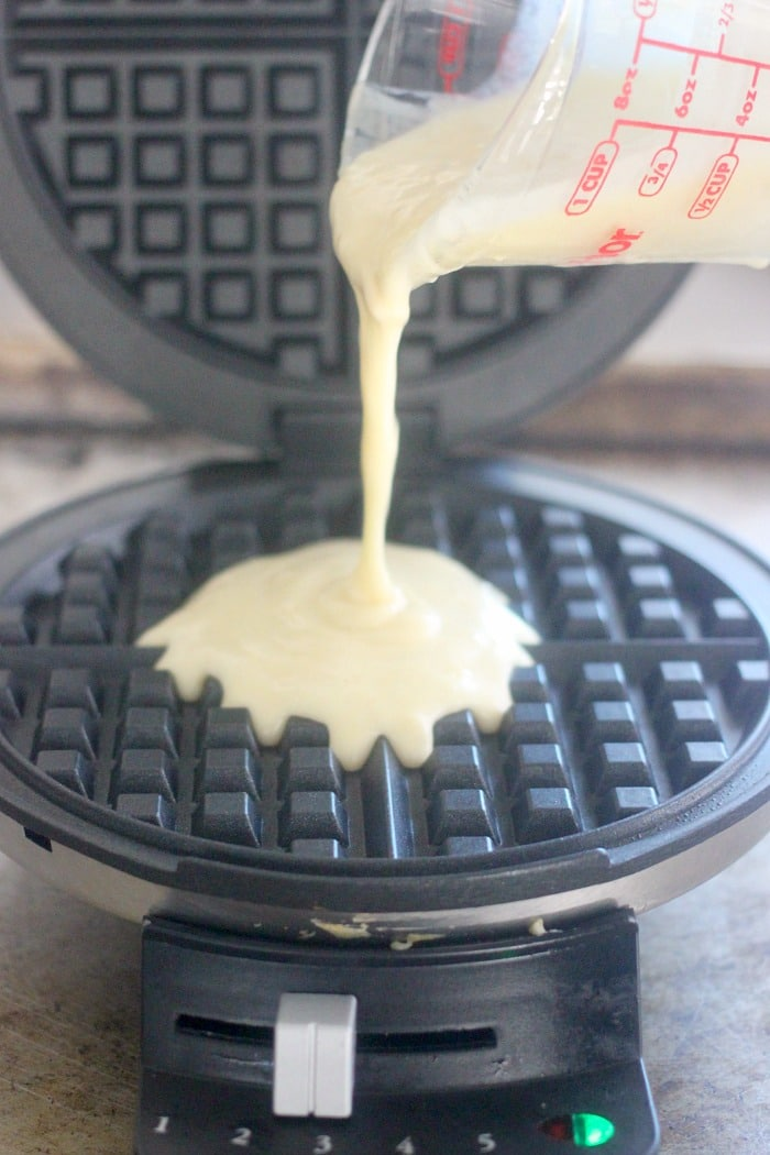 Pouring the batter from the easy waffle recipe into the waffle maker