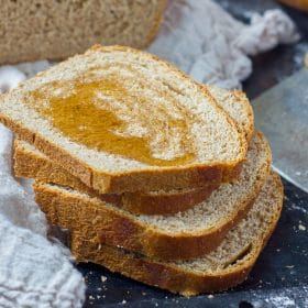 Slices of honey whole wheat bread with honey drizzled on top