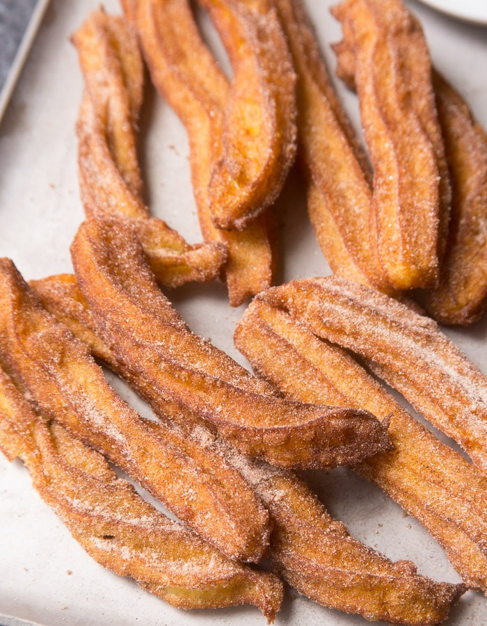 Platter of homemade churros that have been dipped in cinnamon and sugar